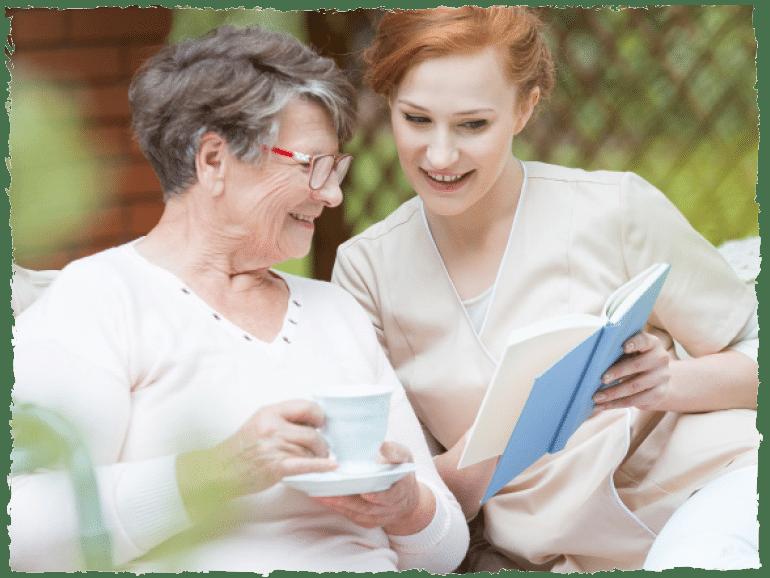 Pflegerin zeigt einer älteren Dame ein Buch