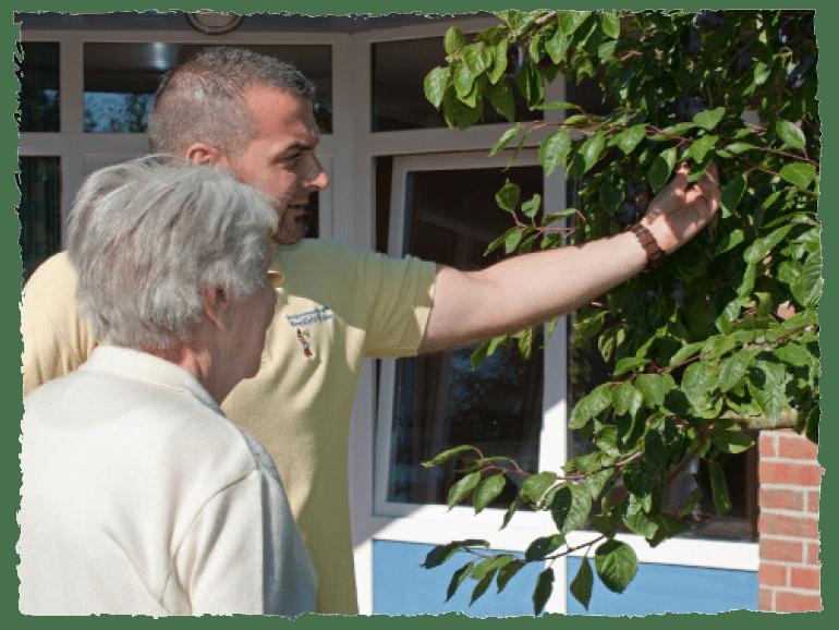 Pfleger zeigt Seniorin einen Baum