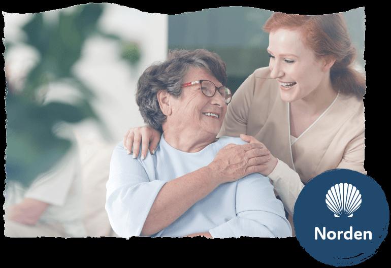 """Ältere Frau und Pflegerin lachen gemeinsam. Symbolbild für die Leistung """"Betreutes Wohnen""""."""
