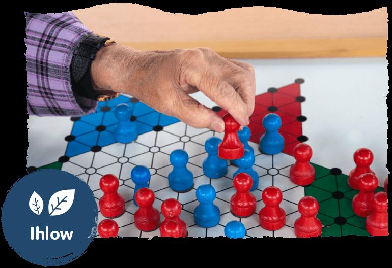 Die Leistung Betreuungsangebote im Seniorenwohnpark Nordlicht. Ältere Frau spielt ein Brettspiel. Im Vordergrund ist das Logo des Standorts Ihlow.