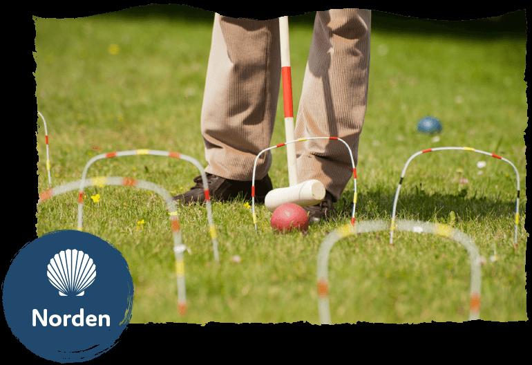 Die Leistung Freizeitservice im Seniorenwohnpark Nordlicht. Ein Mann spielt Croquet im Garten.