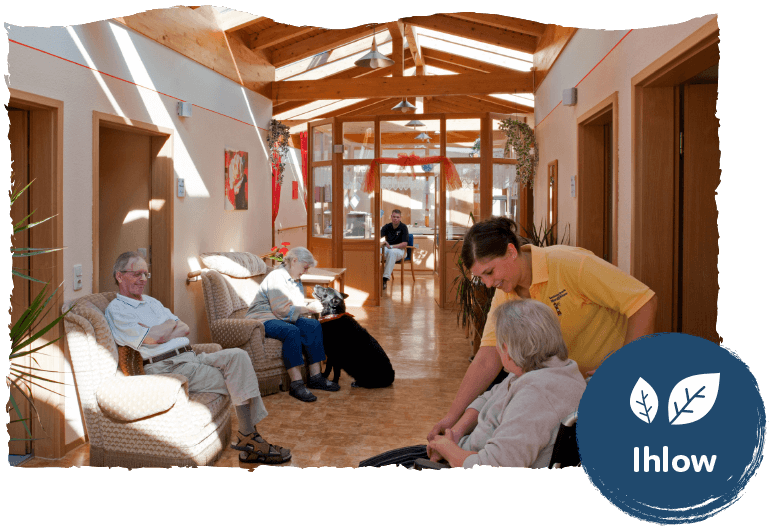 Ältere Leute beisammen in einem Flur mit der Unterstützung von Pflegern. Im Vordergrund das Logo des Standorts Ihlow