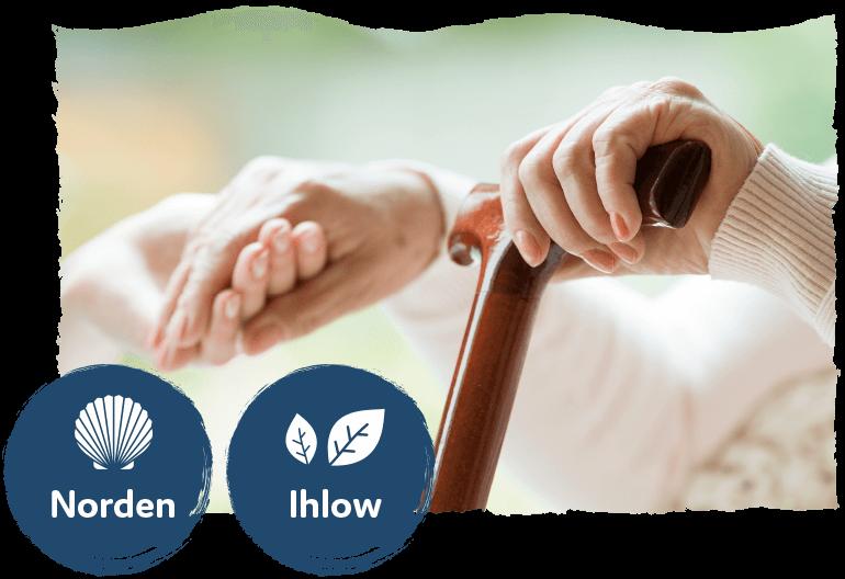 Hände einer ältere Frau halten einen Gehstock und eine helfende Hand mit dem Logo der Standorte Norden und Ihlow