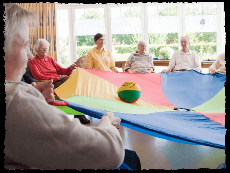 Ältere Menschen spielen mit einer Pflegerin gemeinsam Spiele.