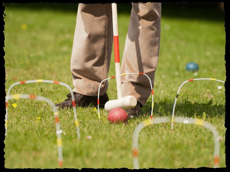 Ein Mann spielt Croquet im Garten.