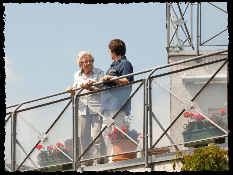 Gespräch zwischen Seniorin und Pflegerin auf dem Balkon des Standorts Norden
