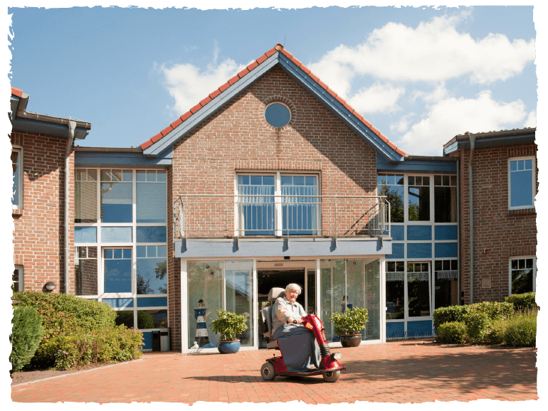 Aussenbereich des Seniorenwohnparks Nordlicht. Eine Frau auf einem Rollator steht vor der Eingangstür.