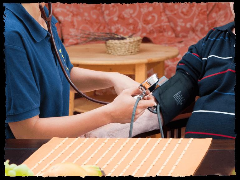 Pflegerin misst Bluthochdruck bei älterem Mann.
