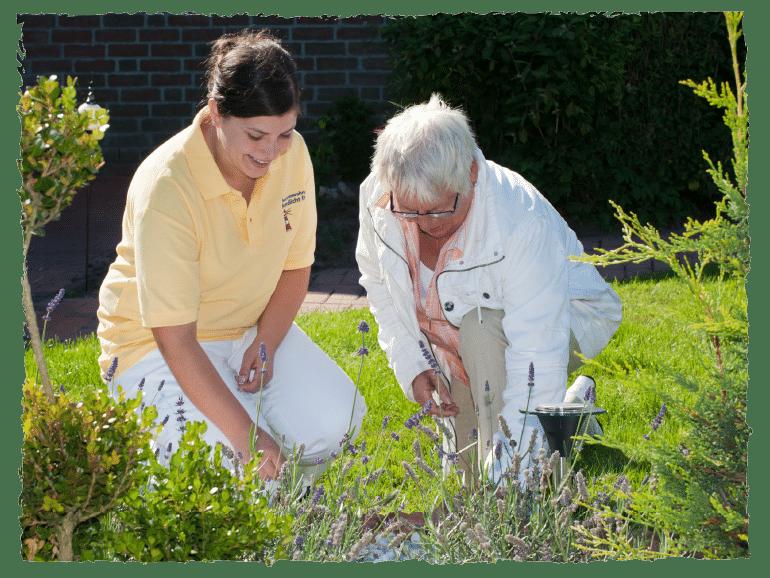 Ältere Frau mit Pflegerin im Garten.