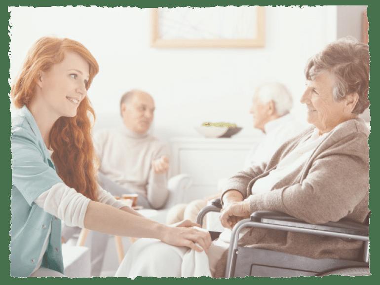 Pflegerin und älteren Dame lächeln sich an. Im Hintergrund sind zwei ältere Männer im Gespräch.